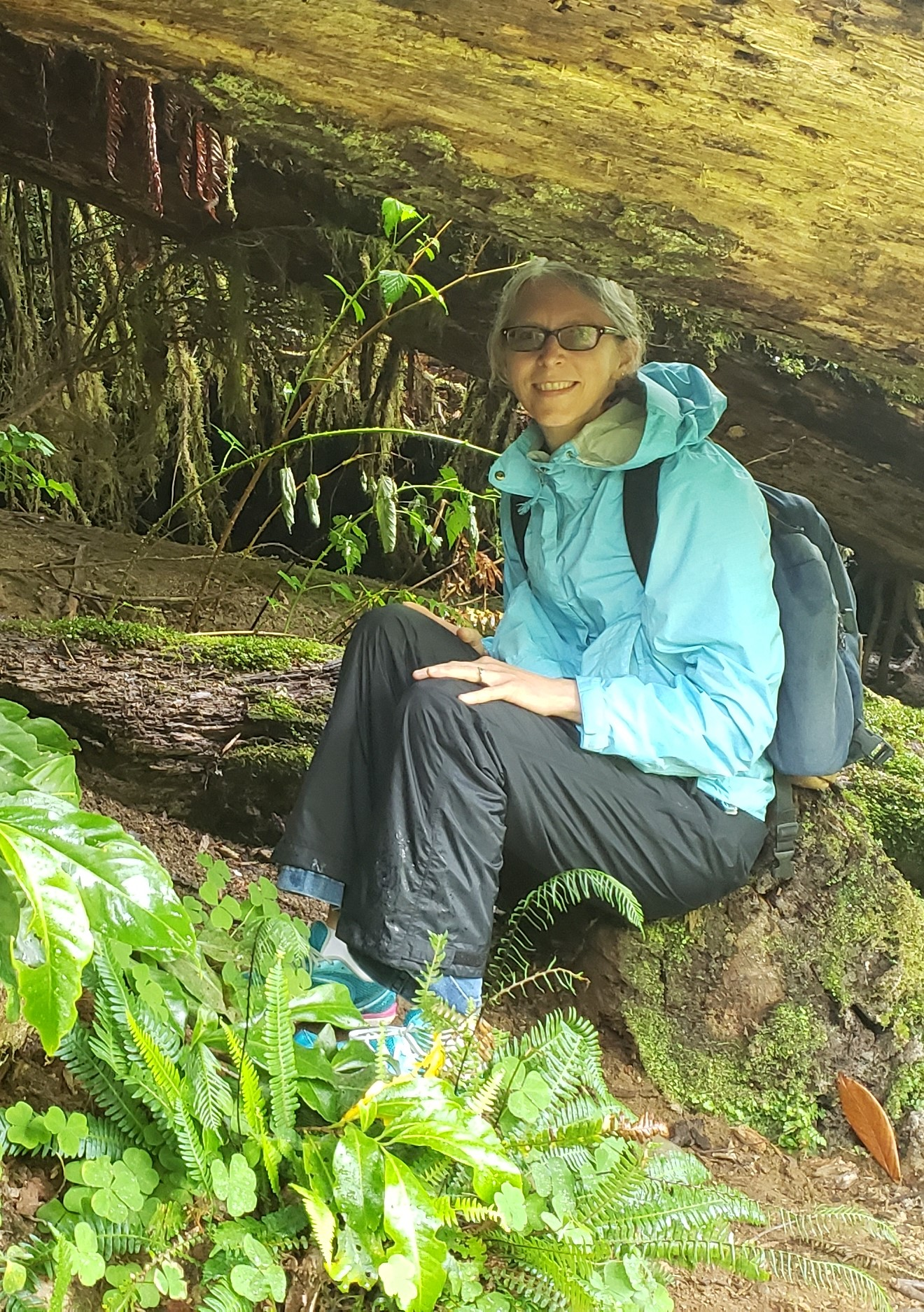 A smiling woman sitting under a log.